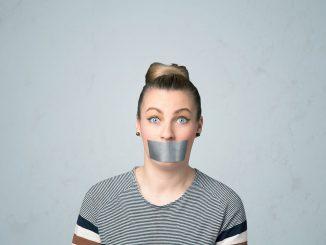 Kvinne med teip over munnen