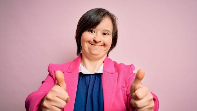 Kvinne med Down syndrom viser tommer opp