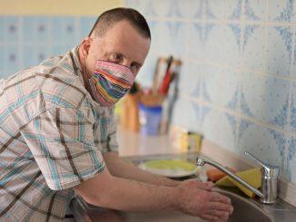 Mann med down syndrom med munnbind vasker hender