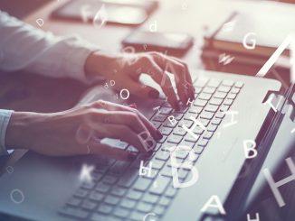 Hender som skriver på en laptop