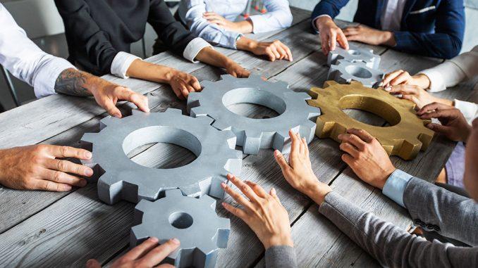 Mange hender som setter sammen tannhjul - Teamarbeid