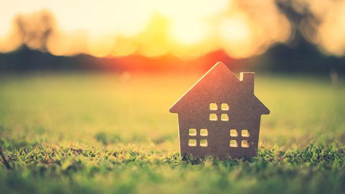 En liten modell av et hus på en gressmatte med solnedgang i bakgrunn