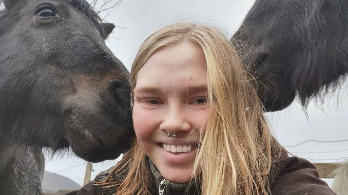 Jente som smiler med to hester