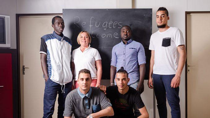 Flyktninger som står samlet i et klasserom