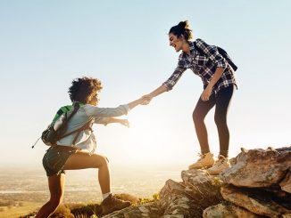 To jenter som hjelper hverandre opp på en fjelltopp