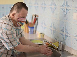 Mann med down syndrom vasker hendene