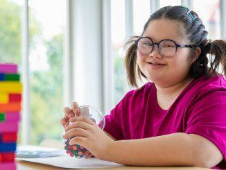 Asiateis jente med Down Syndrom i en læresituasjon